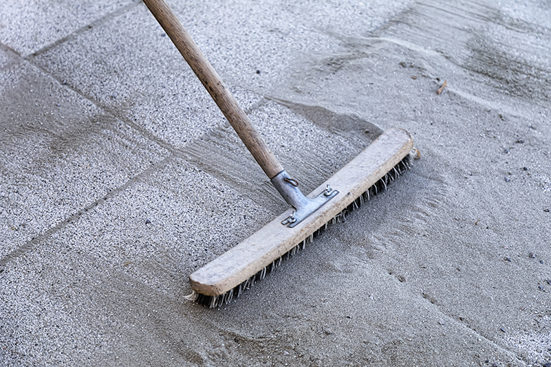 A broom is sweeping polymeric sand into the joints of a newly laid paver patio